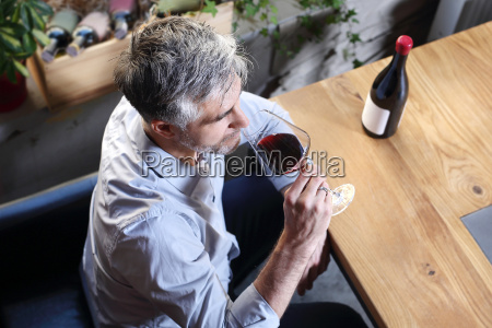 handsome middle aged man drinking wine
