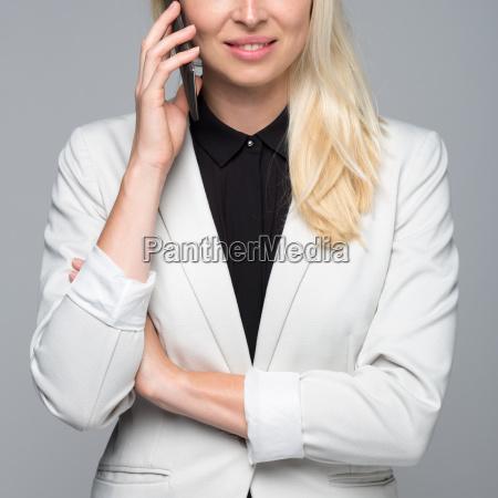 beautiful young caucasian businesswoman talking on
