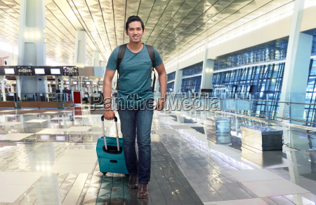 handsome asian traveler walking with bag