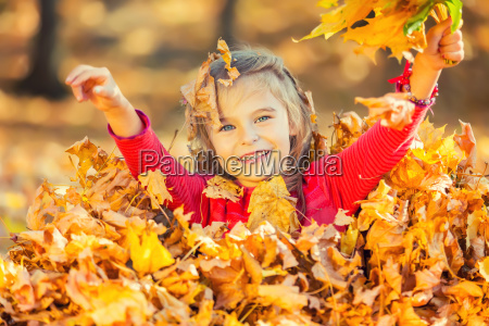 happy little girl plays with autumn