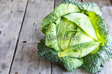 raw savoy cabbage on wooden background