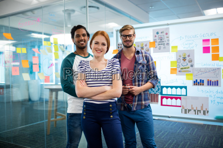 smiling creative business team standing against