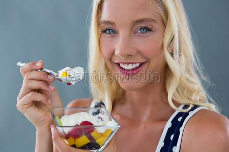 beautiful woman eating fruit salad in