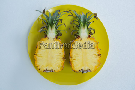 overhead of two halved pineapple in