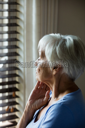 thoughtful senior woman looking out from