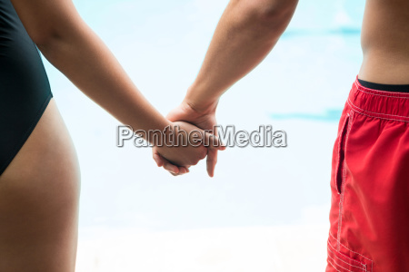 couple holding hands at poolside