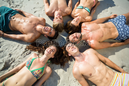 happy friends sunbathing on shore at