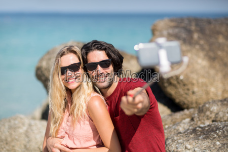couple taking selfie with monopod at