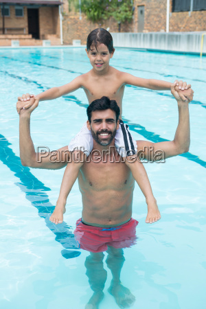 father carrying son on shoulder in