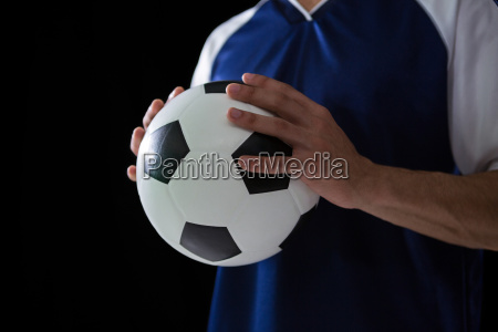 mid-section, of, football, player, holding, football - 23052063