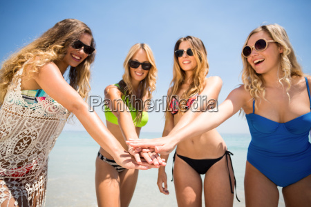 female friends in bikinis stacking hands