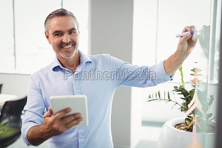 portrait of smiling executive using digital