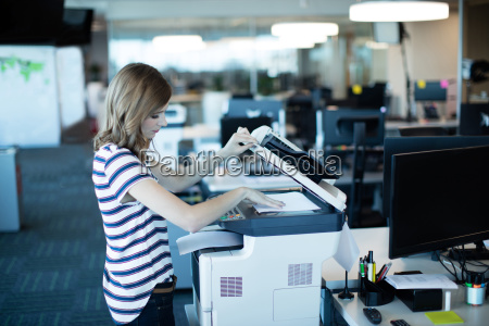 young businesswoman using copy machine in