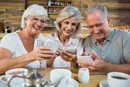 group of senior friends using mobile