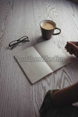 businesswoman writing on book at office