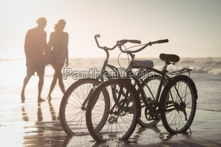 bicycles parking on shore with couple