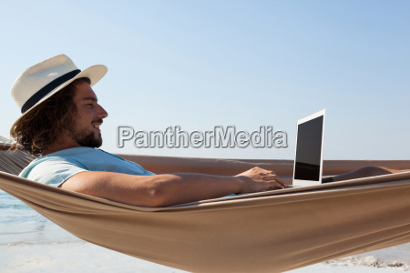 man using laptop while relaxing on