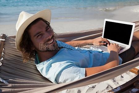 smiling man using laptop while relaxing
