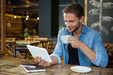 smiling man using digital tablet while