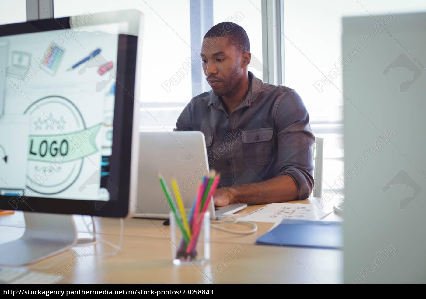serious, graphic, designer, using, laptop, in - 23058843
