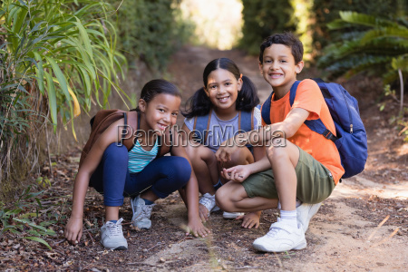 smiling friends crouching on field at
