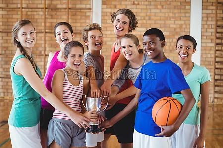 smiling high school kids holding trophy
