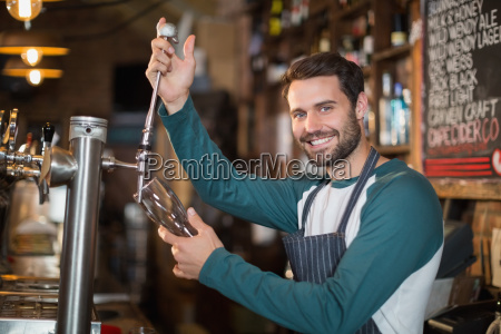 portrait of bartender pouring beer from