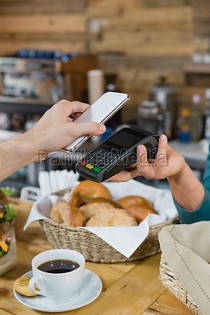 customer paying bill through smartphone using