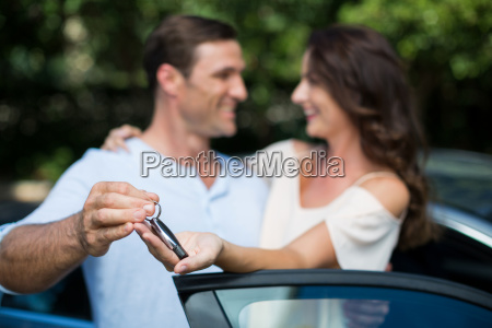 man giving key to woman by