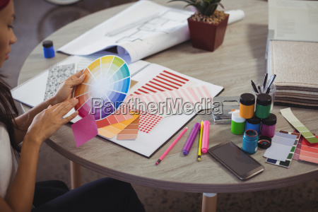 businesswoman holding colour swatch at office