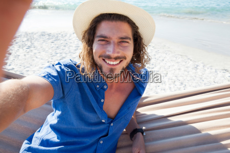 man taking selfie while relaxing on
