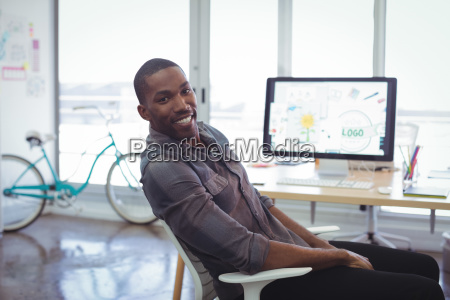 smiling businessman sitting in brightly lit