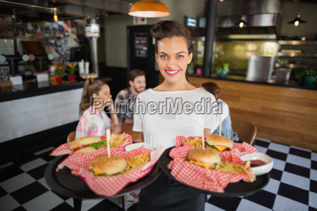 waitress serving burger while customers sitting