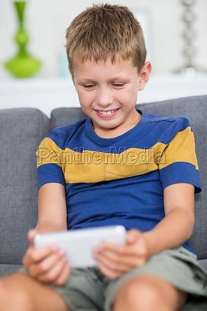 happy boy sitting on sofa and