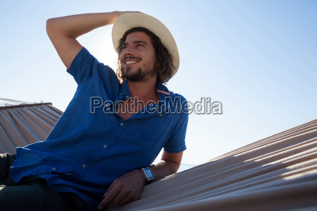 thoughtful man relaxing on hammock at