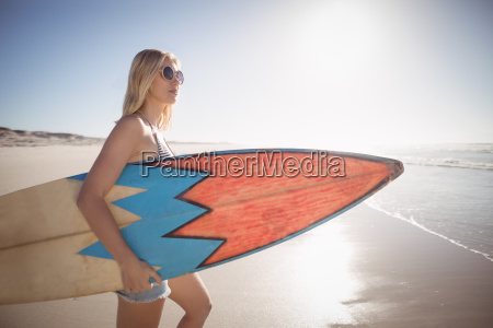 woman carrying surfboard at beach during