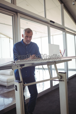 mature businessman standing by workbench in