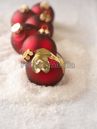 old red christmas baubles in snow
