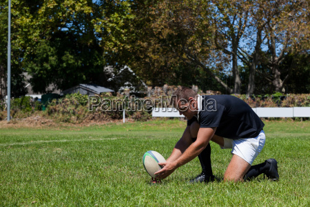 rugby player playing with ball on