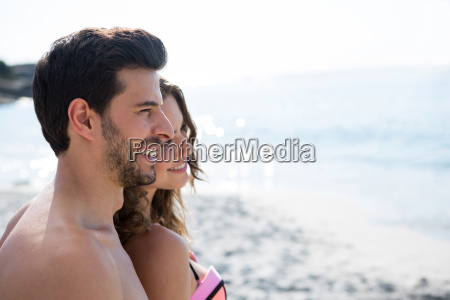 thoughtful young couple standing at beach