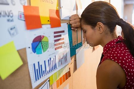 depressed female executive leaning on bulletin