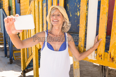 smiling woman holding smart phone while