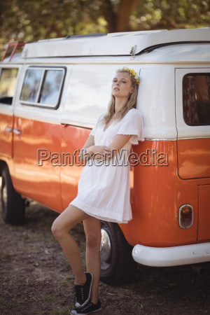 thoughtful woman leaning on van