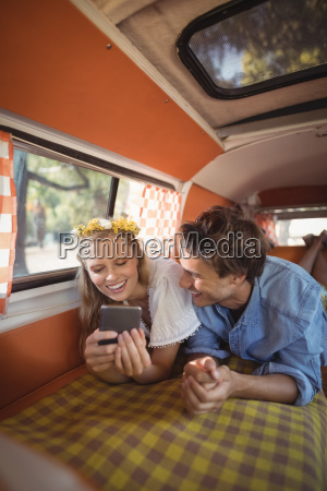 happy woman with man using phone