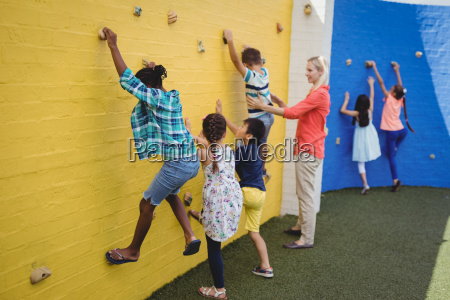 trainer assisting kids in climbing wall