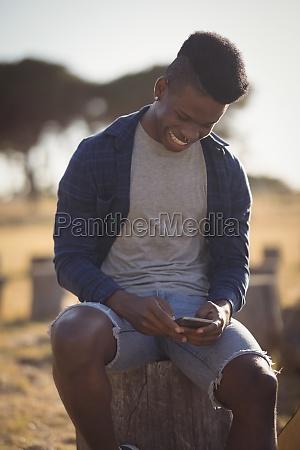 smiling man using smart phone while