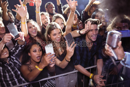 cheerful crowd photographing performer at nightclub