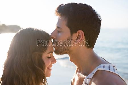 young man kissing girlfriend forehead at