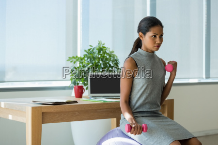 beautiful executive lifting dumbbells while exercising