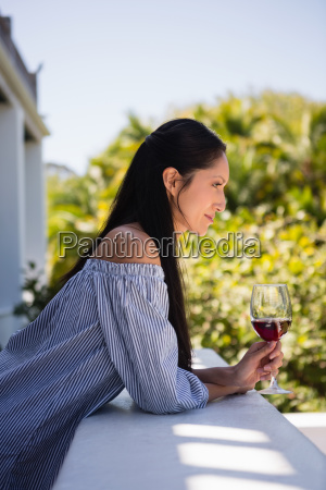 thoughtful young woman holding red wine
